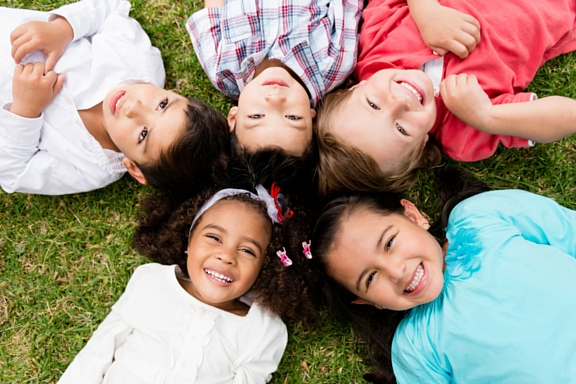 Diverse group of children lying on the grass
