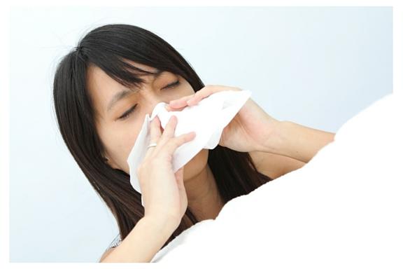 Woman sneezing because of spring allergies