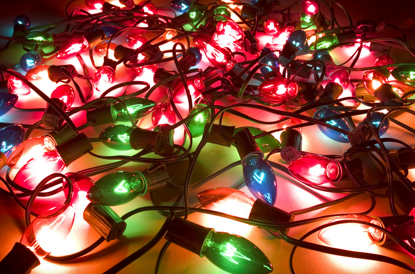 A traditional set of Christmas tree holiday lights illuminated and lying on the floor