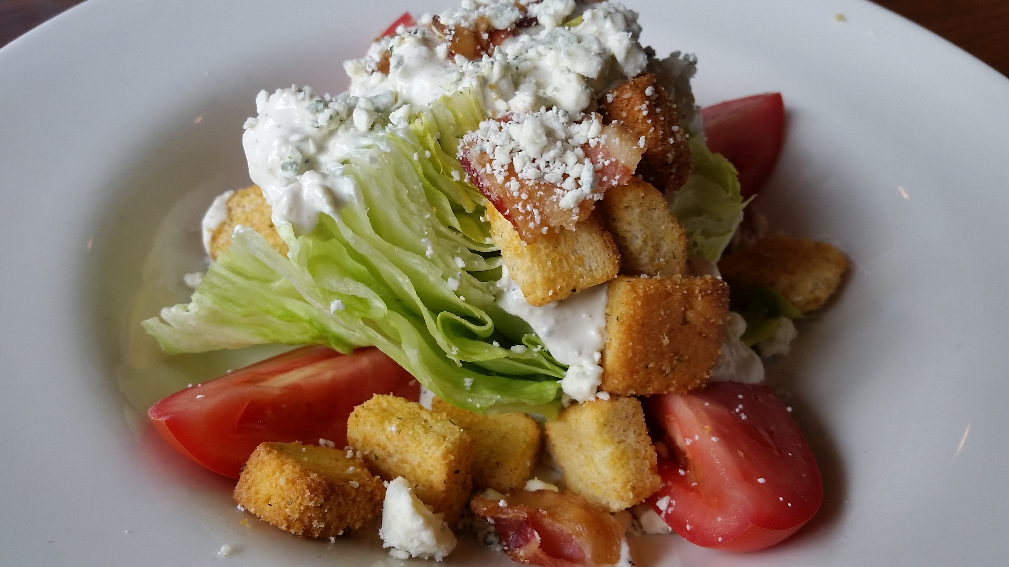 Wedge salad with lettuce, bacon, tomatoes and bleu cheese dressing and croutons at Wintergreen Resort The Edge