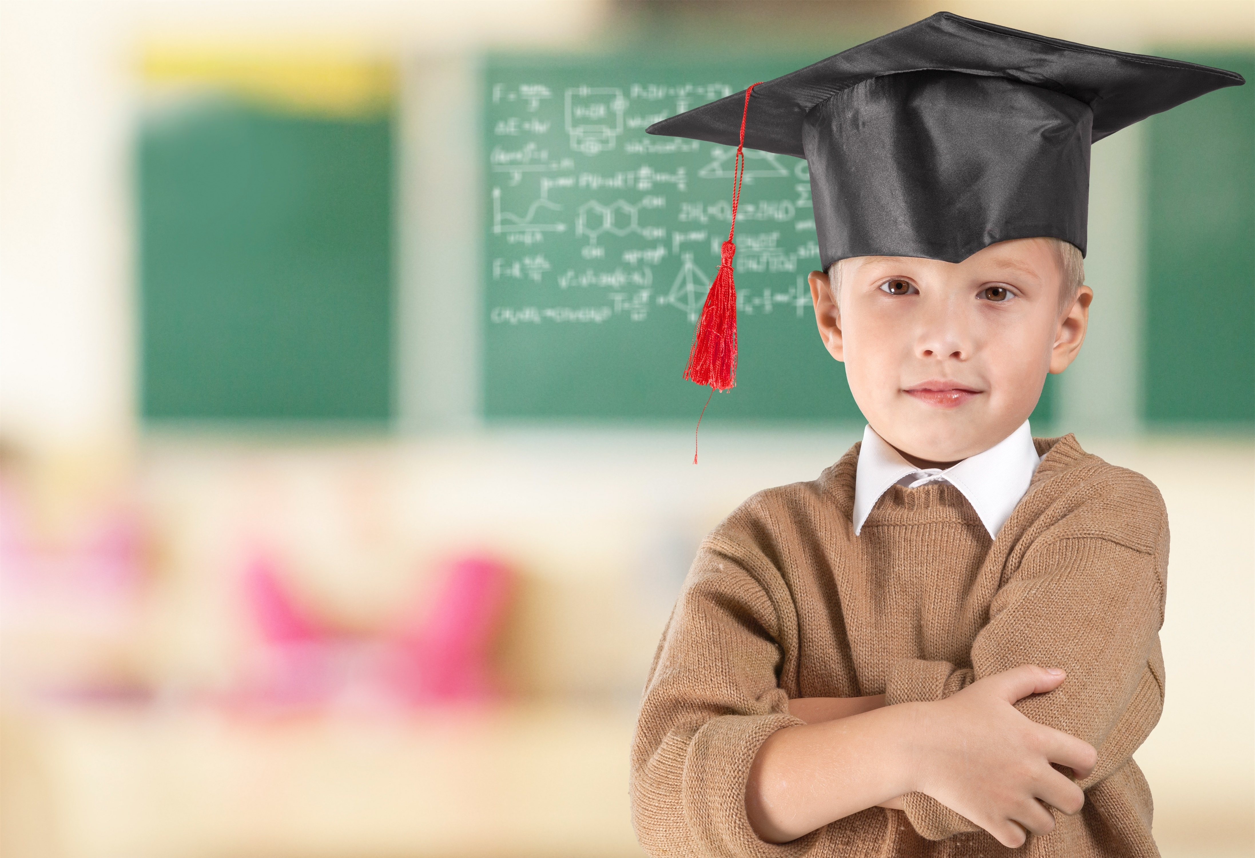 Young Boy In Graduation Cap With Green Blackboard Behind Him