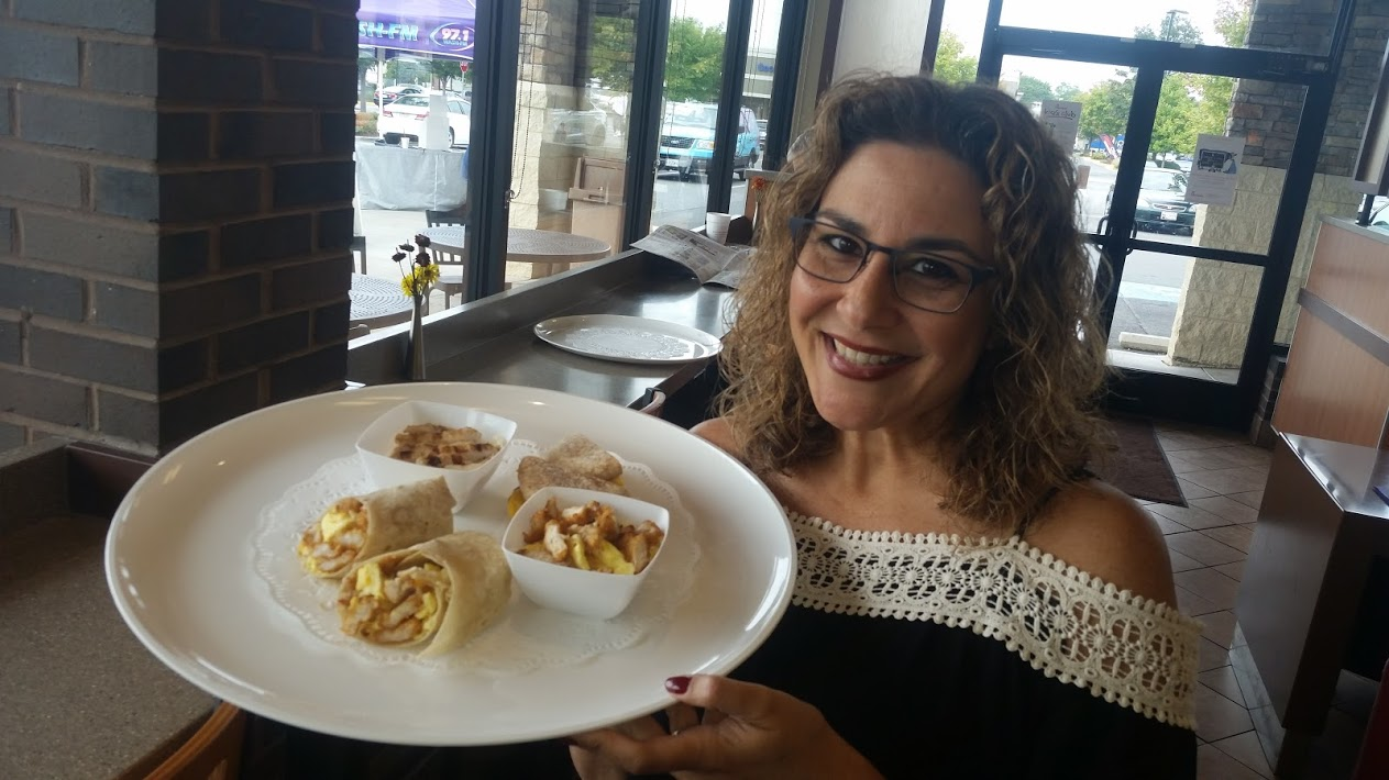 Radio personality Chilli Amar of WASH-FM with a tray of new Chick-fil-A breakfast foods