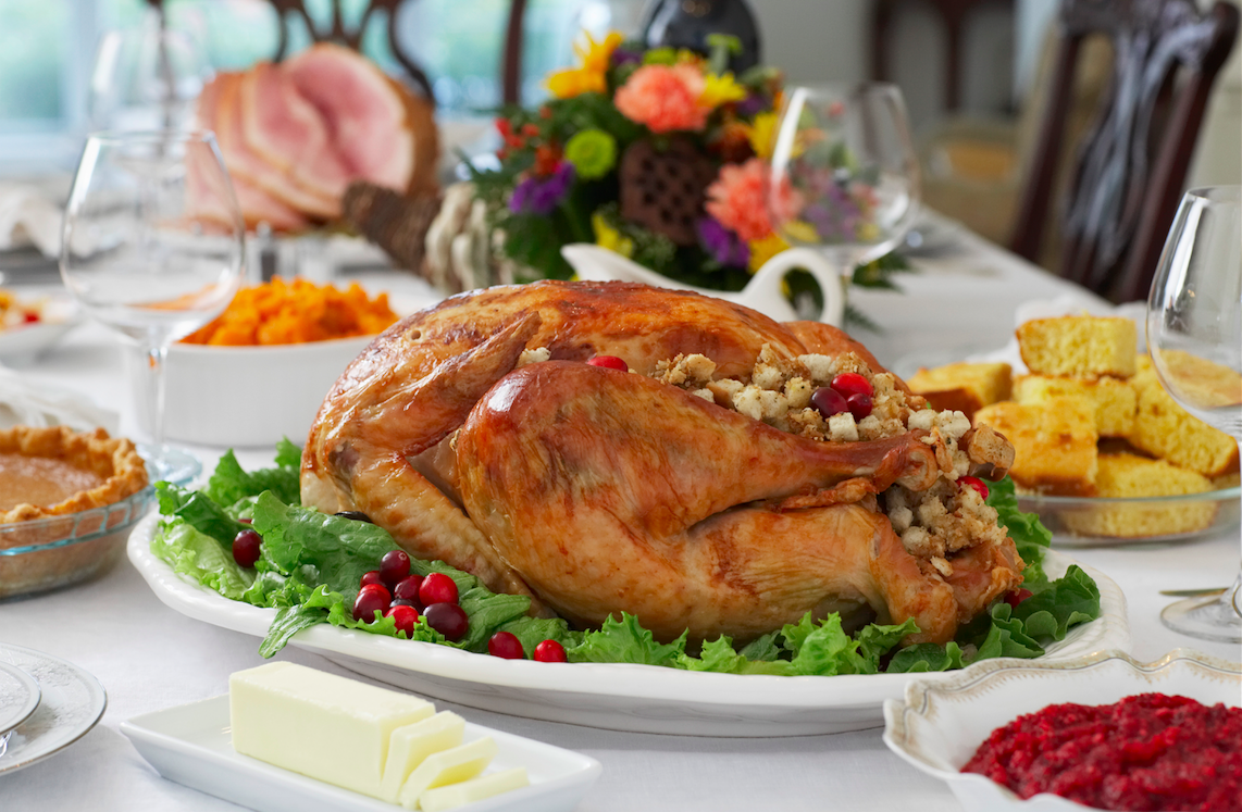 A nice table set with a traditional Thanksgiving meal of turkey, cornbread, cranberry sauce, and more