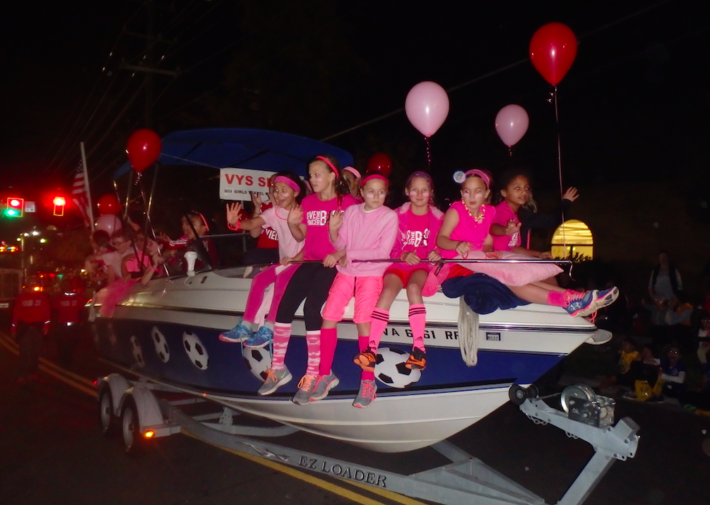 Young girls dressed in pink riding a boat at the Vienna, Virginia, Halloween parade