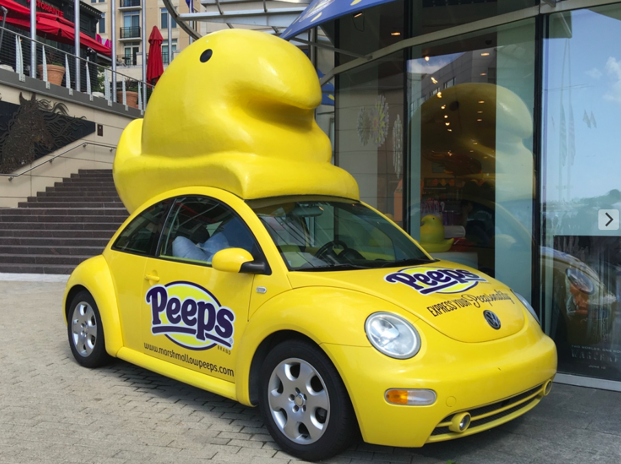 "Yellow VW Beetle car with a big yellow JustBorn company ""marshmallow Peep"" on top, parked at the Peeps & Company store at National Harbor in southern Maryland"