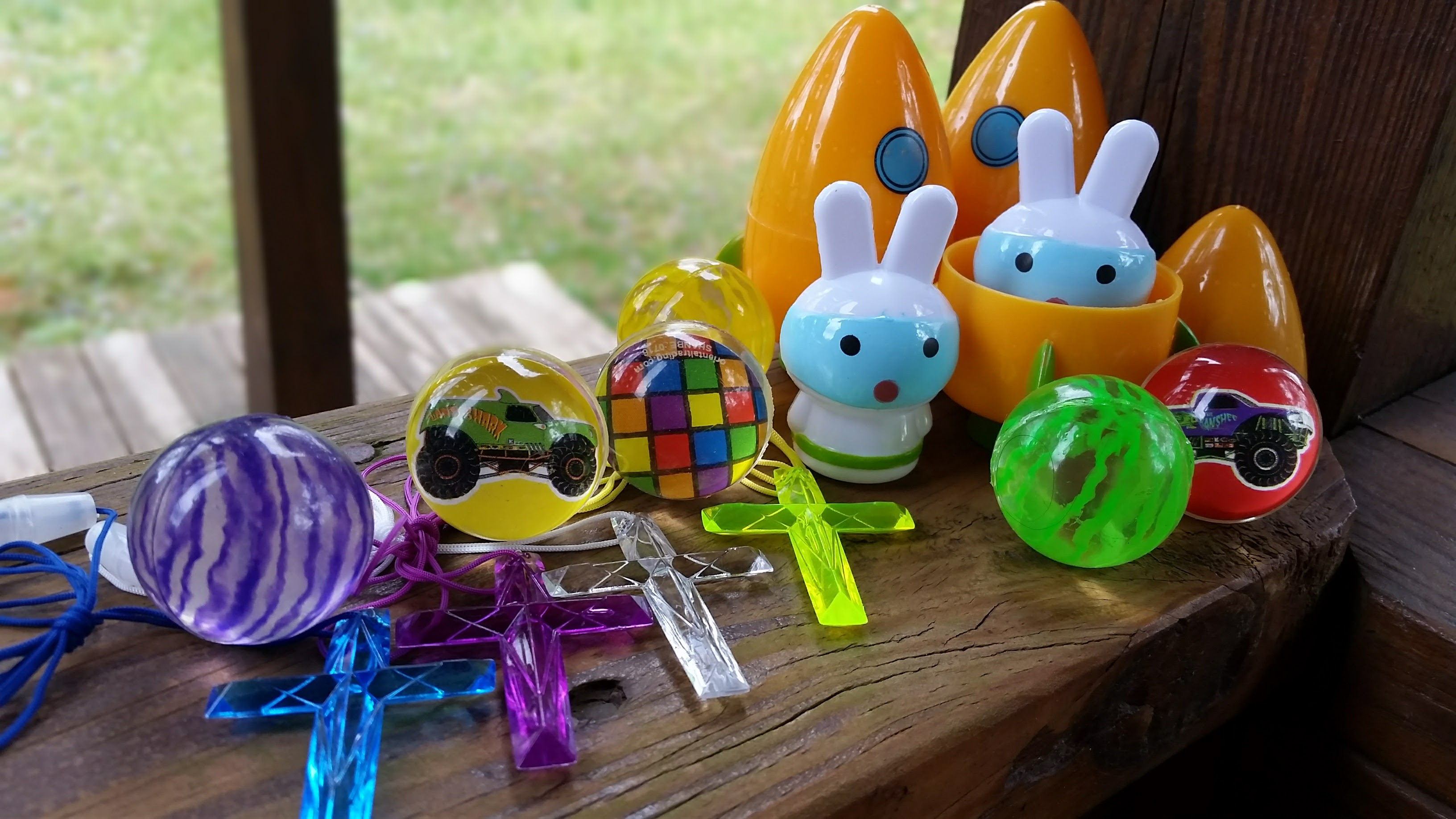 Plastic bunny in carrot spaceship egg, plastic cross necklaces, and bouncy balls for Easter egg hunt, products from Oriental Trading Company