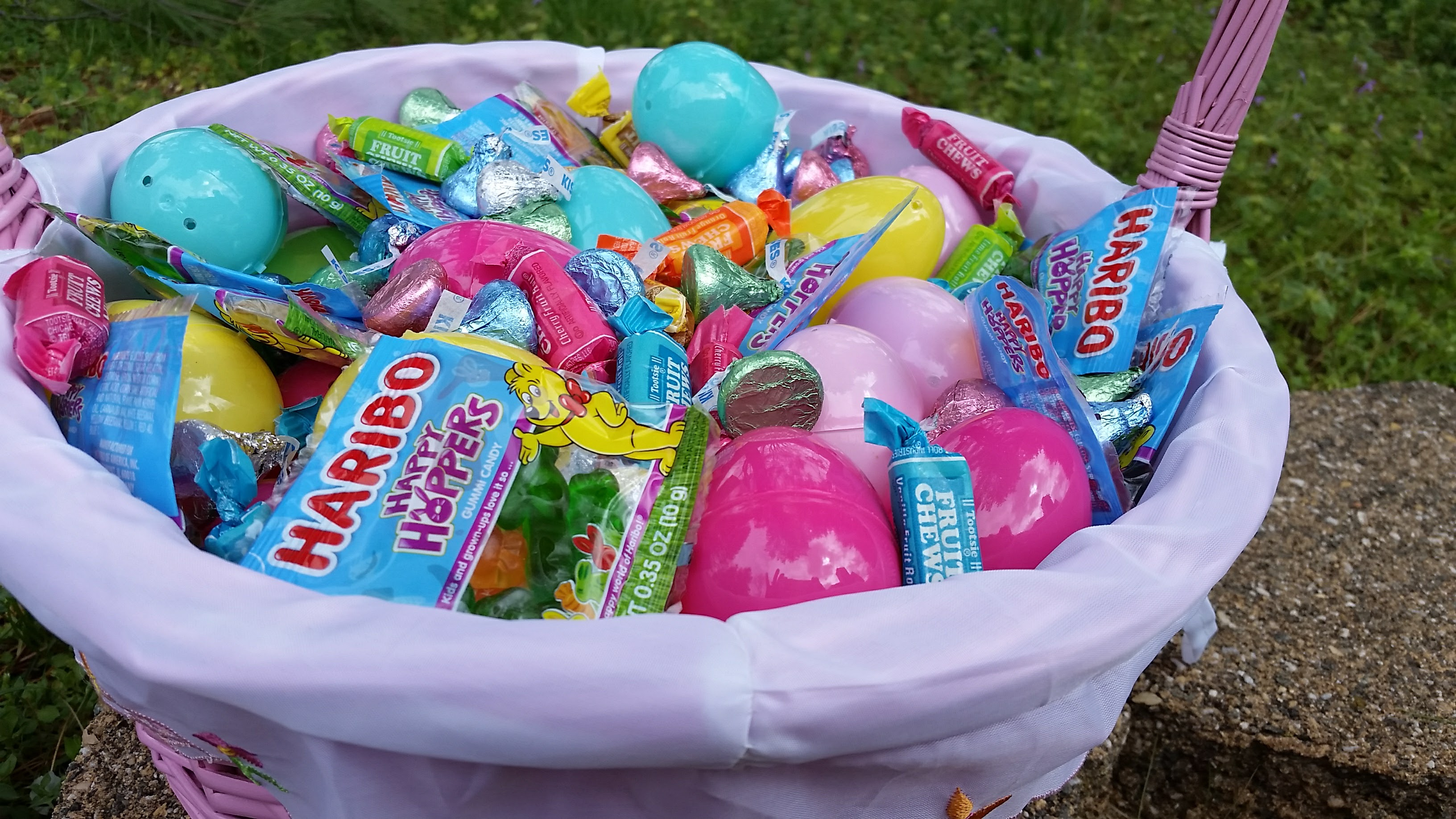 Pink lined Easter basket filled with plastic Easter eggs and candies
