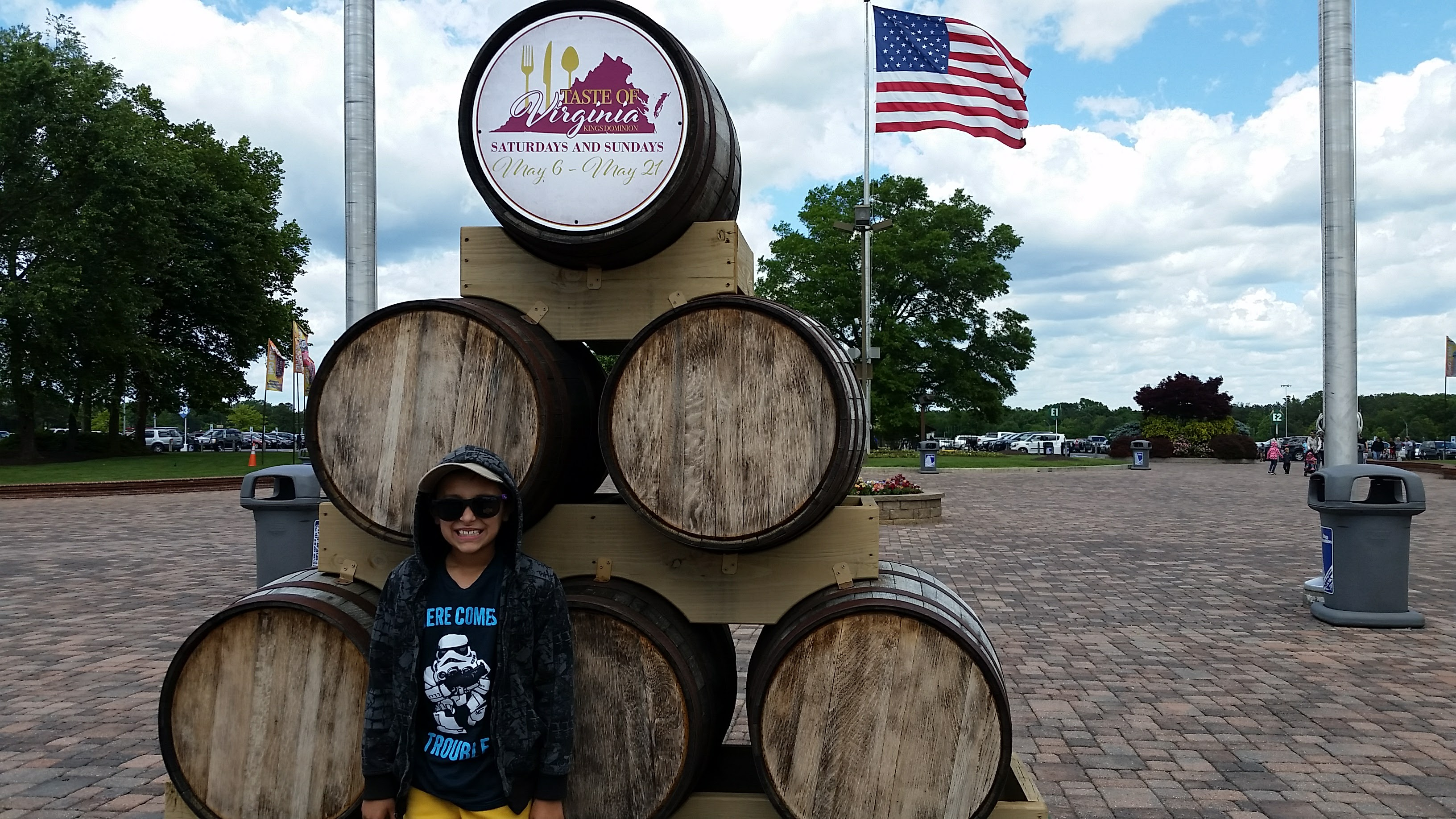Young boy standing in front of wine or whiskey barrels with Taste of Virginia Kings Dominion signs