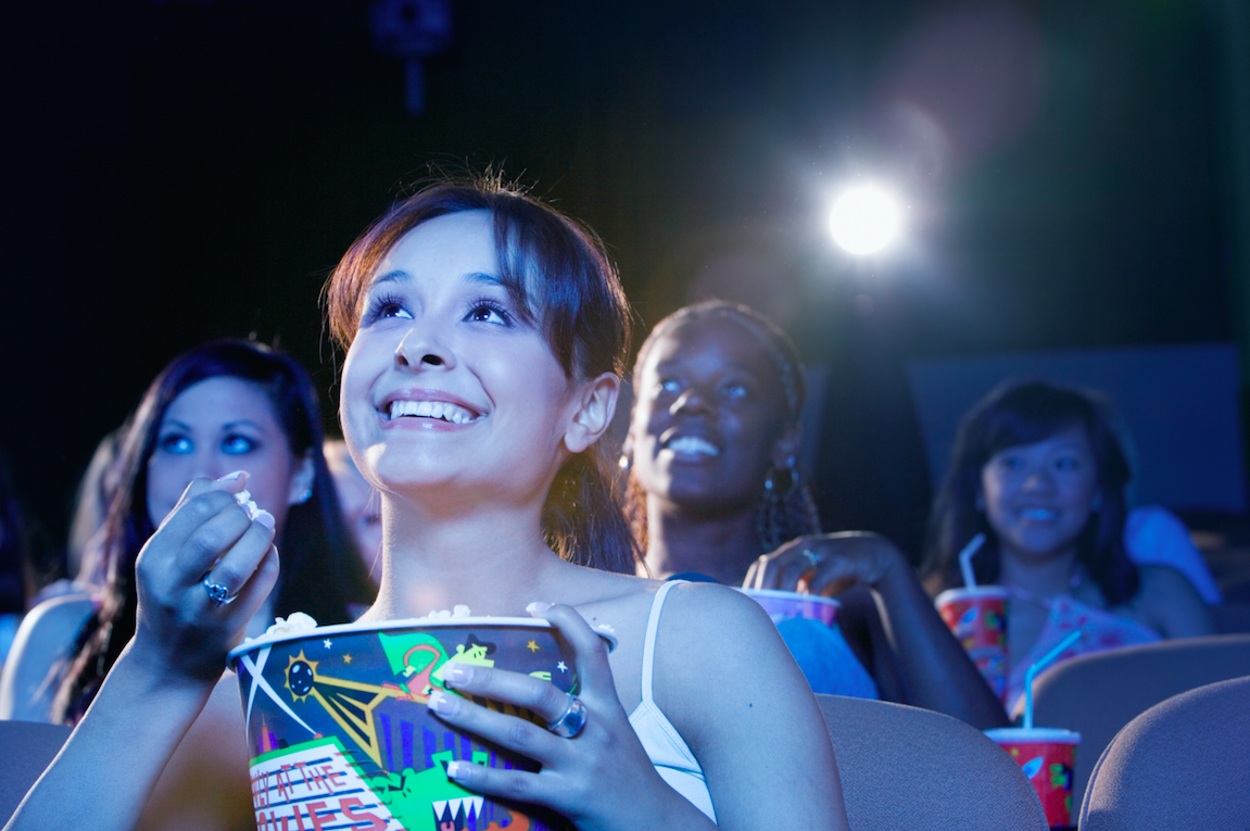 Young women watching a movie and eating popcorn in a theatre