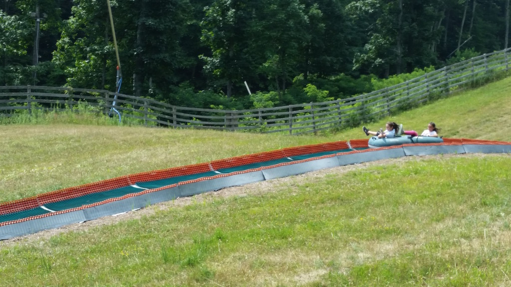 Three girls slide down the track at the Wintergreen Resort summer tubing park