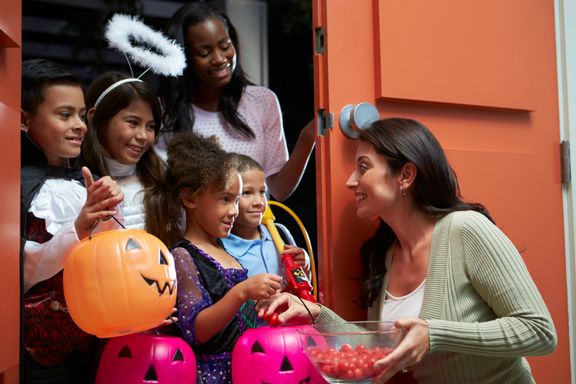 kids of mixed races and ages in costume trick or treating with woman at door handing