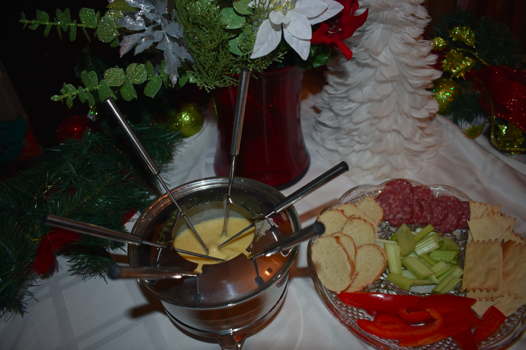 cheese fondue with vegetables, bread, and crackers