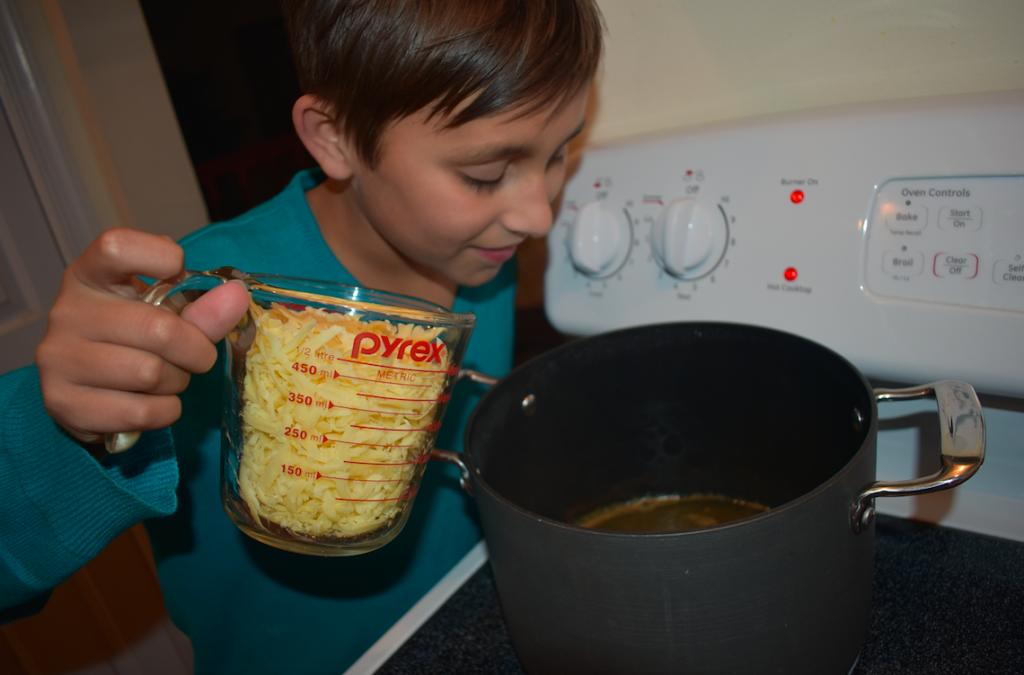 young boy making cheese fondue