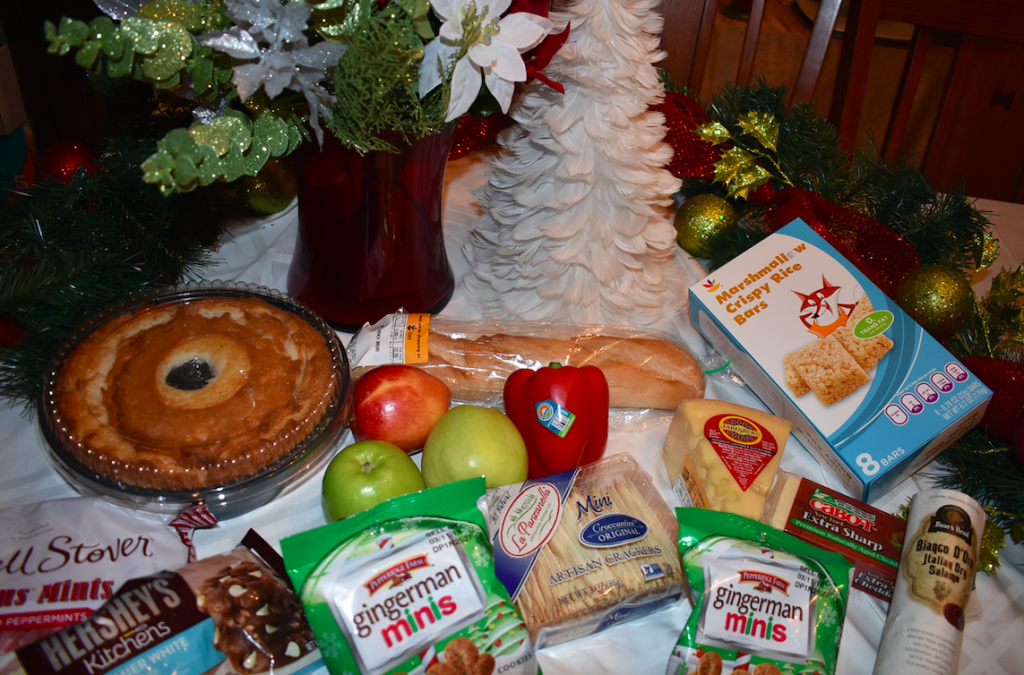 various fondue ingredients for cheese and chocolate fondues with Christmas decorations in background