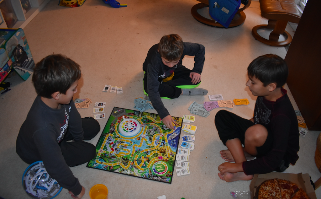 Three boys playing The Game of Life on a living room floor while eating pizza, board games, The Genius of Play
