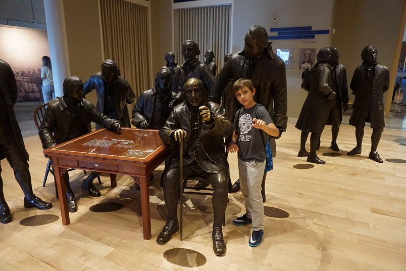 A boy poses with founding father statues, including Benjamin Franklin, at Constitution Center in Philadelphia.