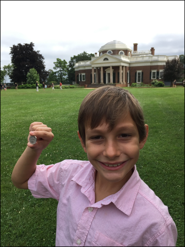 Boy holding up nickel to show Monticello against the Monticello home.