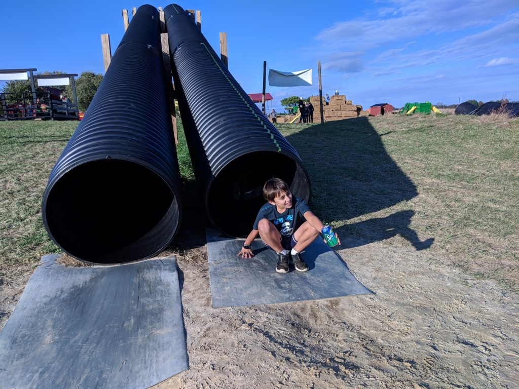 Leaving the tunnel slide at Wayside Farm Fun on a sunny day during the fall festival in northern Virginia