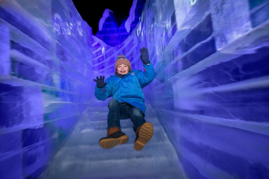 A child smiling as he goes down the ice slide at Christmas on the Potomac ICE! at Gaylord National