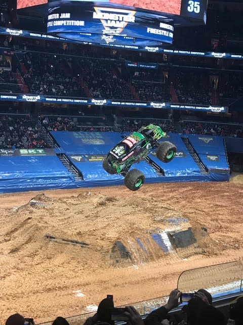 Grave Digger monster truck flipping through the air at a Monster Jam competition in DC, Capital One Arena