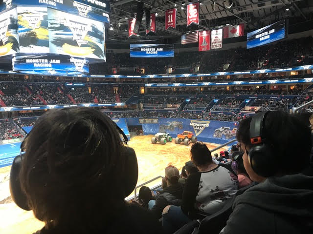 Kids with headphones attend Monster Jam monster truck competition
