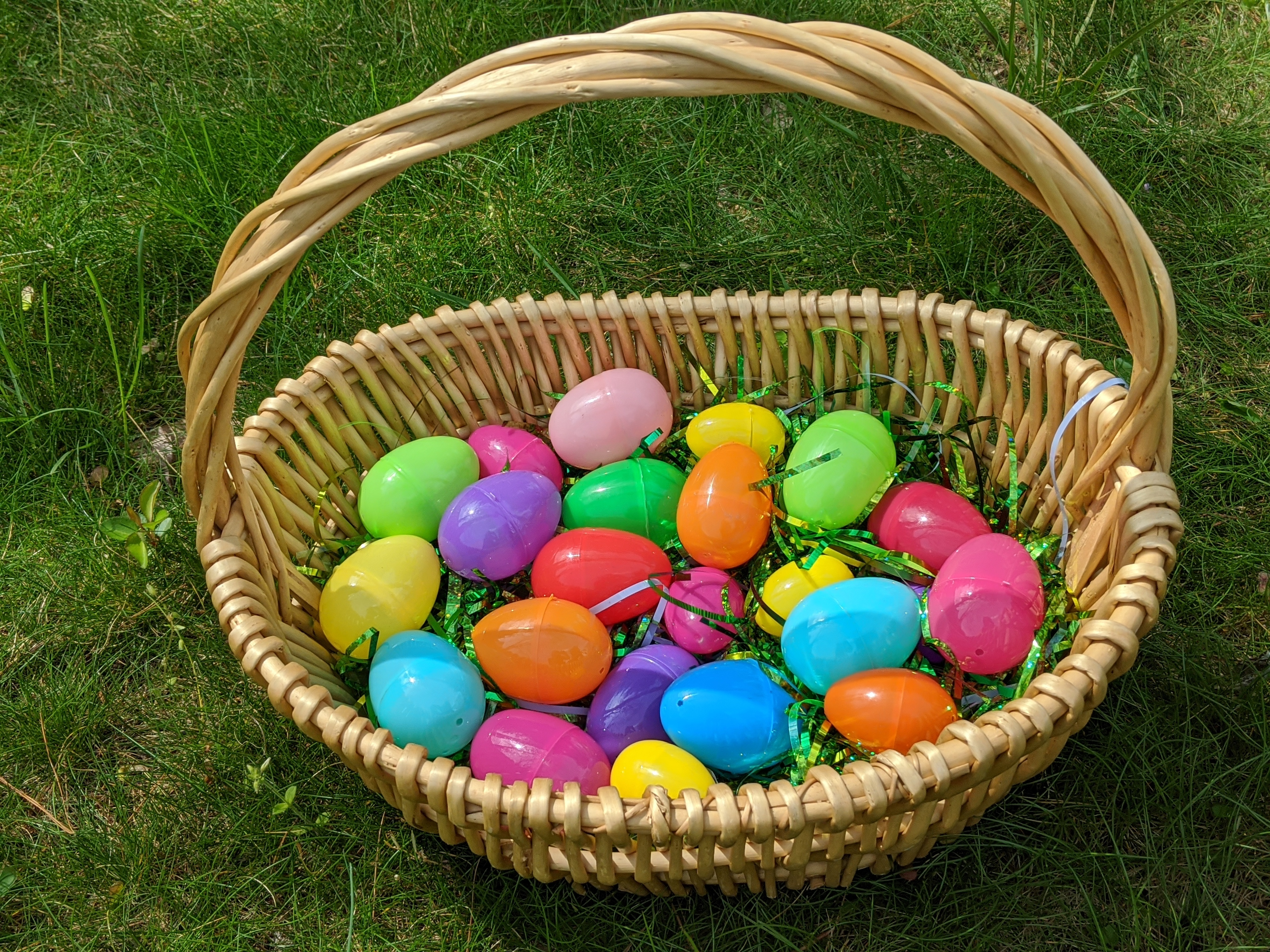 Easter basket filled with decorative grass and plastic Easter eggs for Virtual Egg Hunt